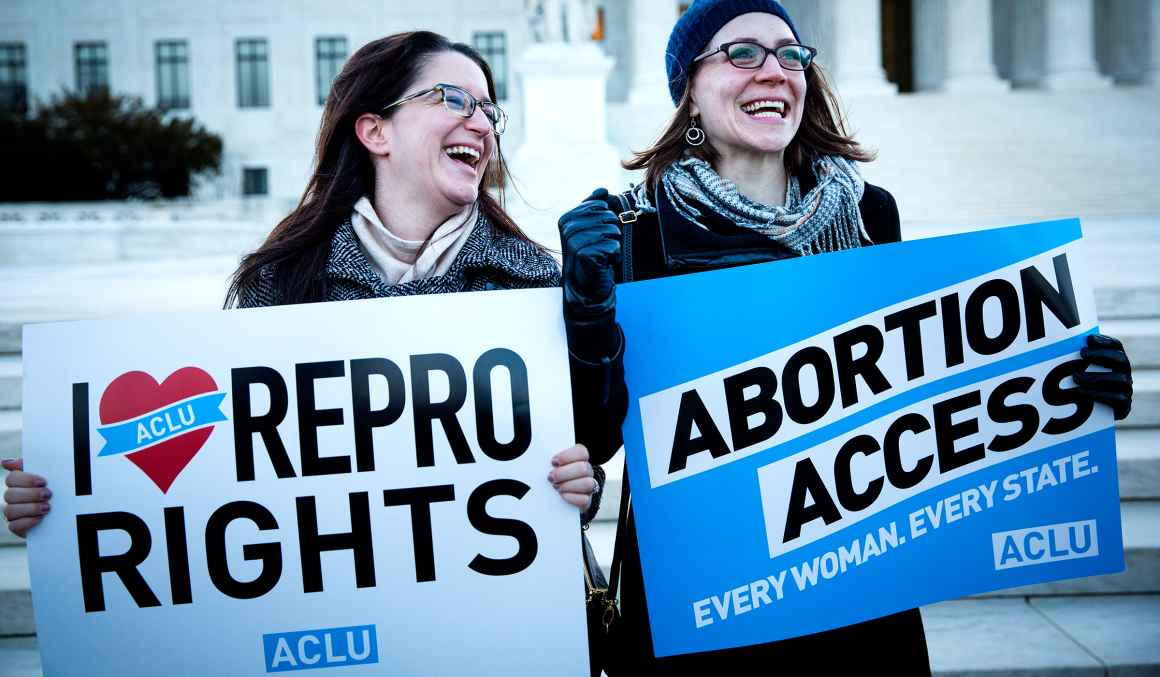 Two women holding abortion access rally signs