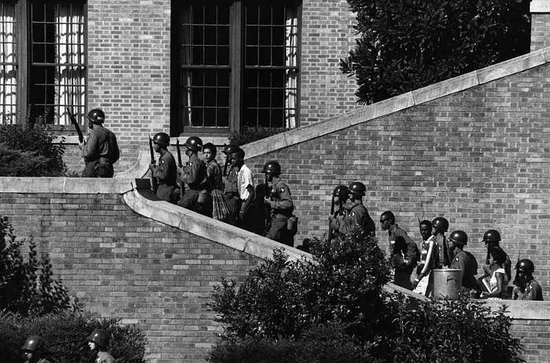 Little Rock Nine enter Central High School under federal troop escort