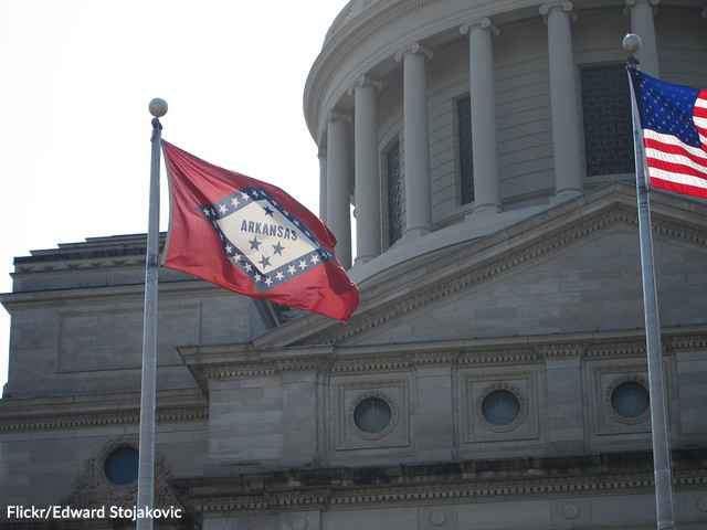 The Arkansas and United States flags in front of the Arkansas State Capitol