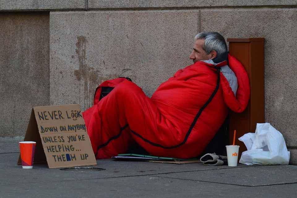 "Homeless man with sign: ""Never look down on anybody unless you're helping them up"""