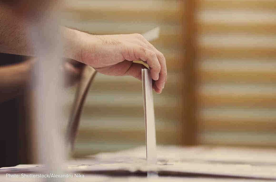 Photo of voter putting a ballot in a ballot box