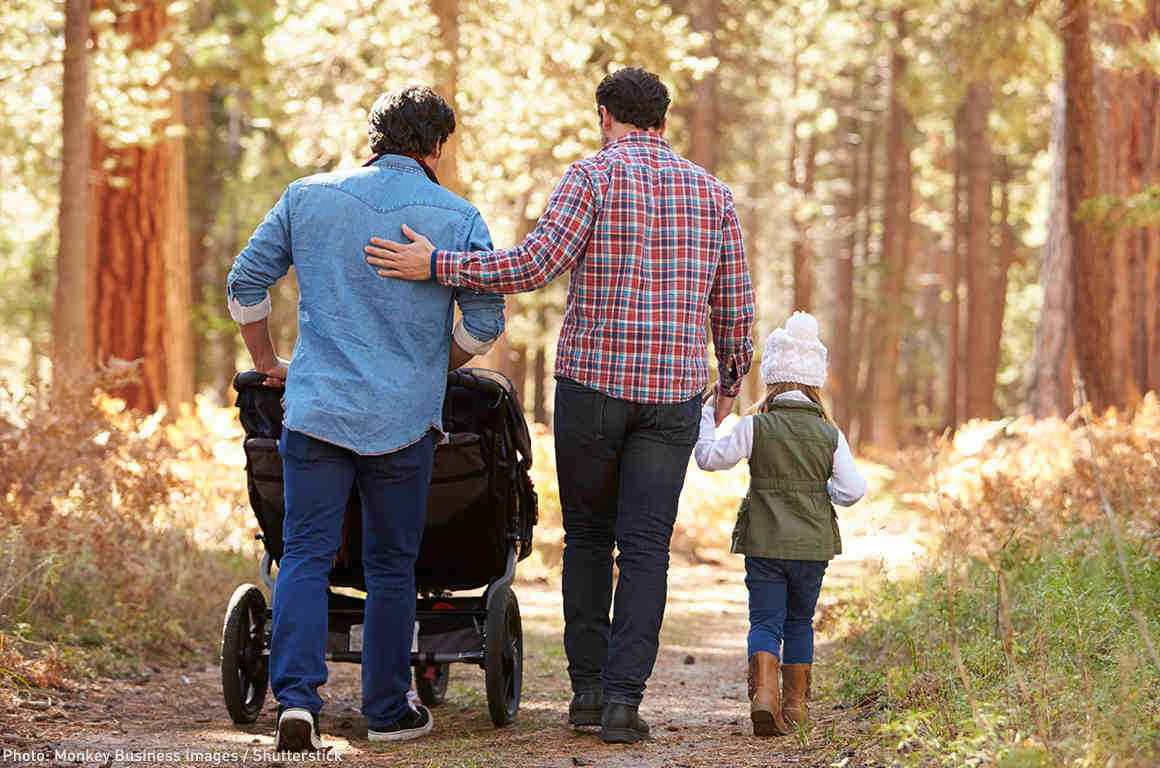 A gay couple walking with their children through the woods