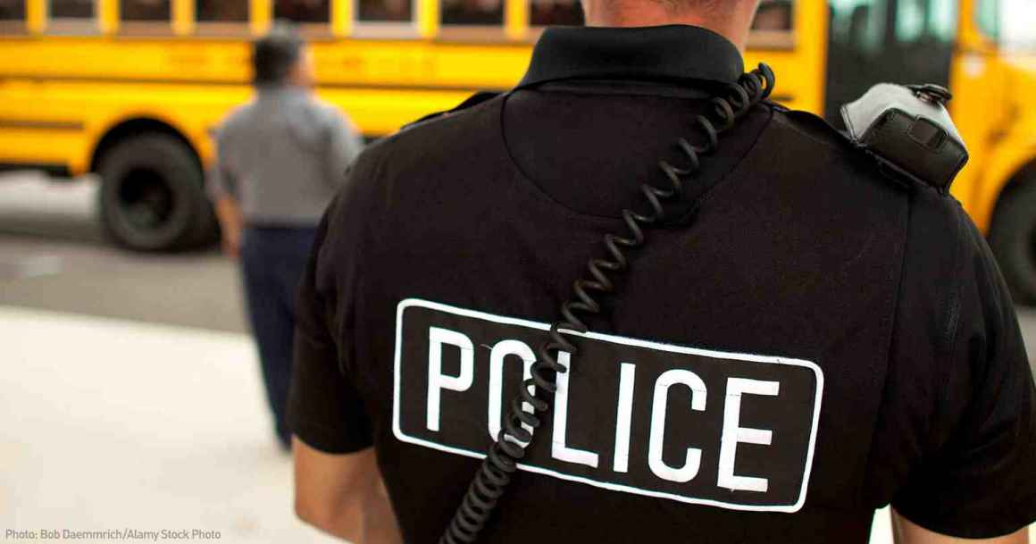 Police officer standing in front of a school bus