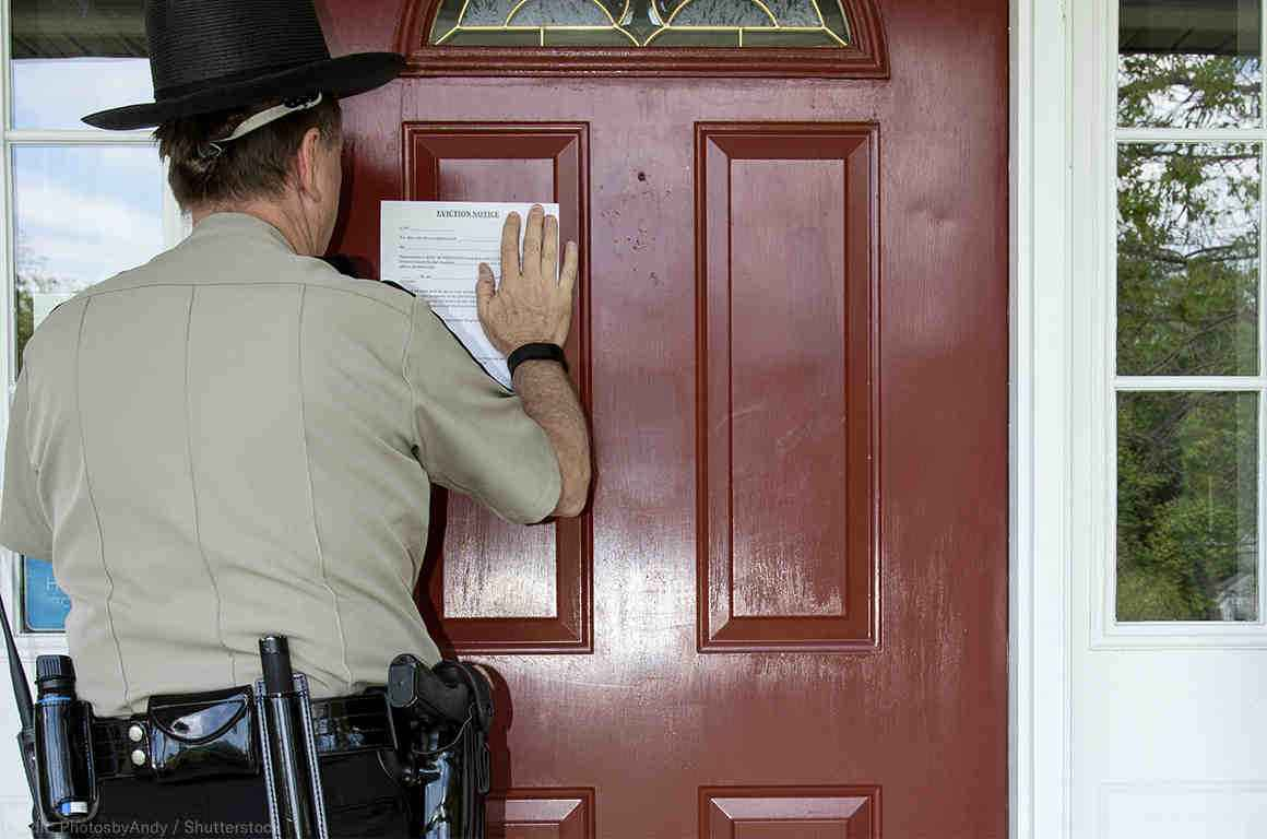Law enforcement officer posting an eviction notice on a door