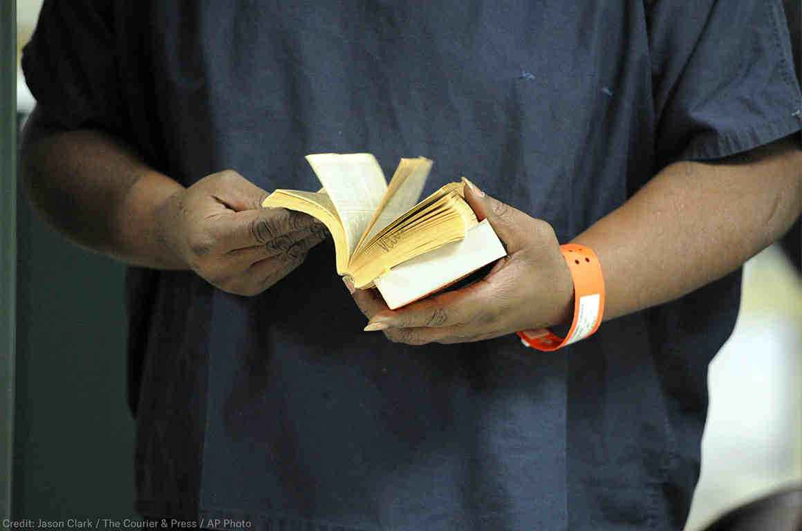 An incarcerated man holds a book