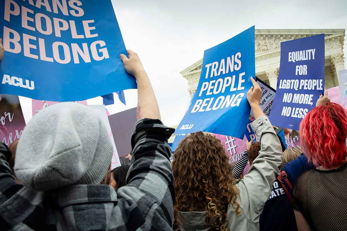"""Protesters hold rally signs reading """"Trans people belong"""" and """"Equality for LGBTQ People"""""""