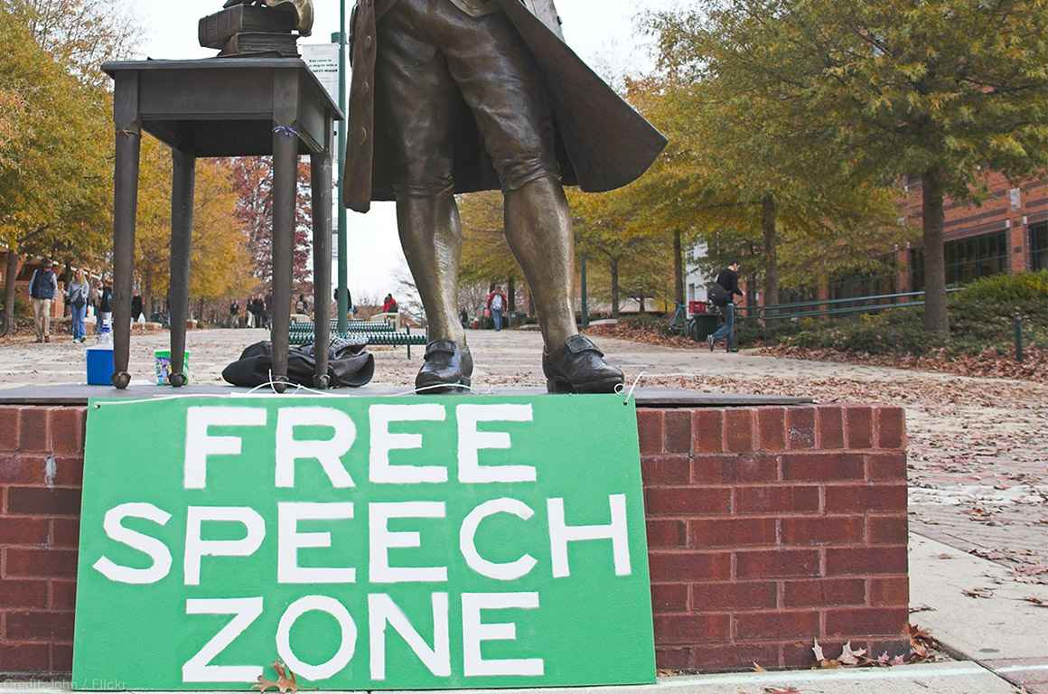 Free speech zone sign in front of statue