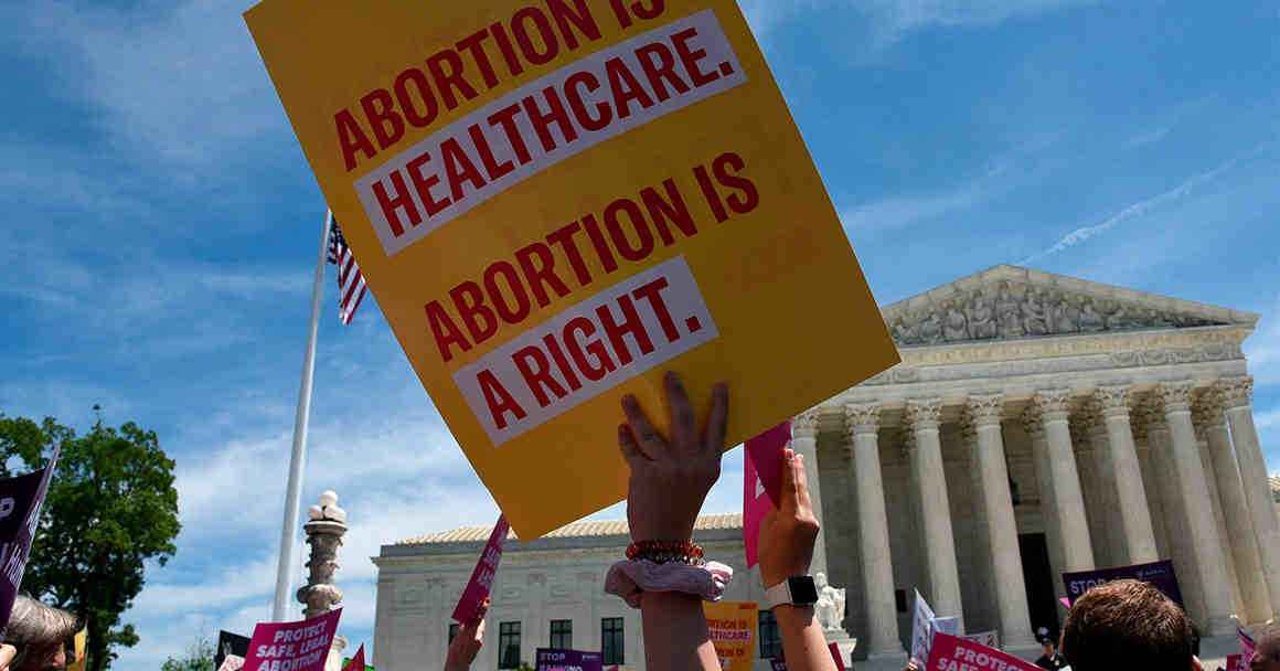 "Protester at the US Supreme Court holding a sign reading ""Abortion is healthcare. Abortion is a right."""