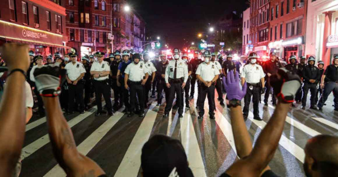 Protesters facing a line of police