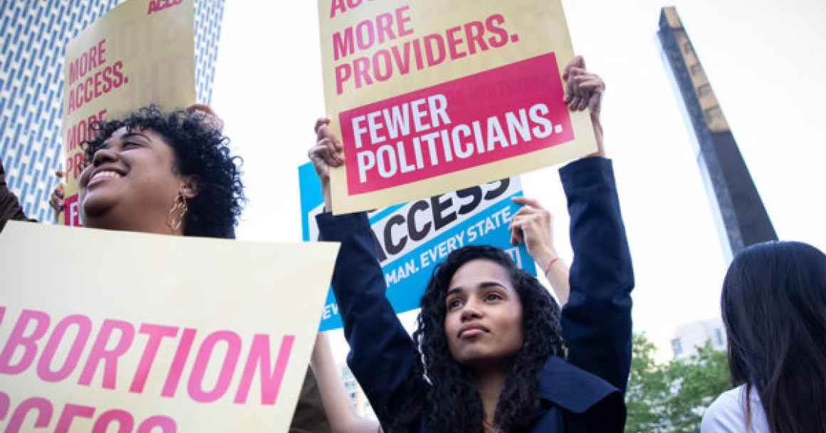 """Young african american woman holding a sign that reads """"More access. More providers. Fewer politicians."""""""